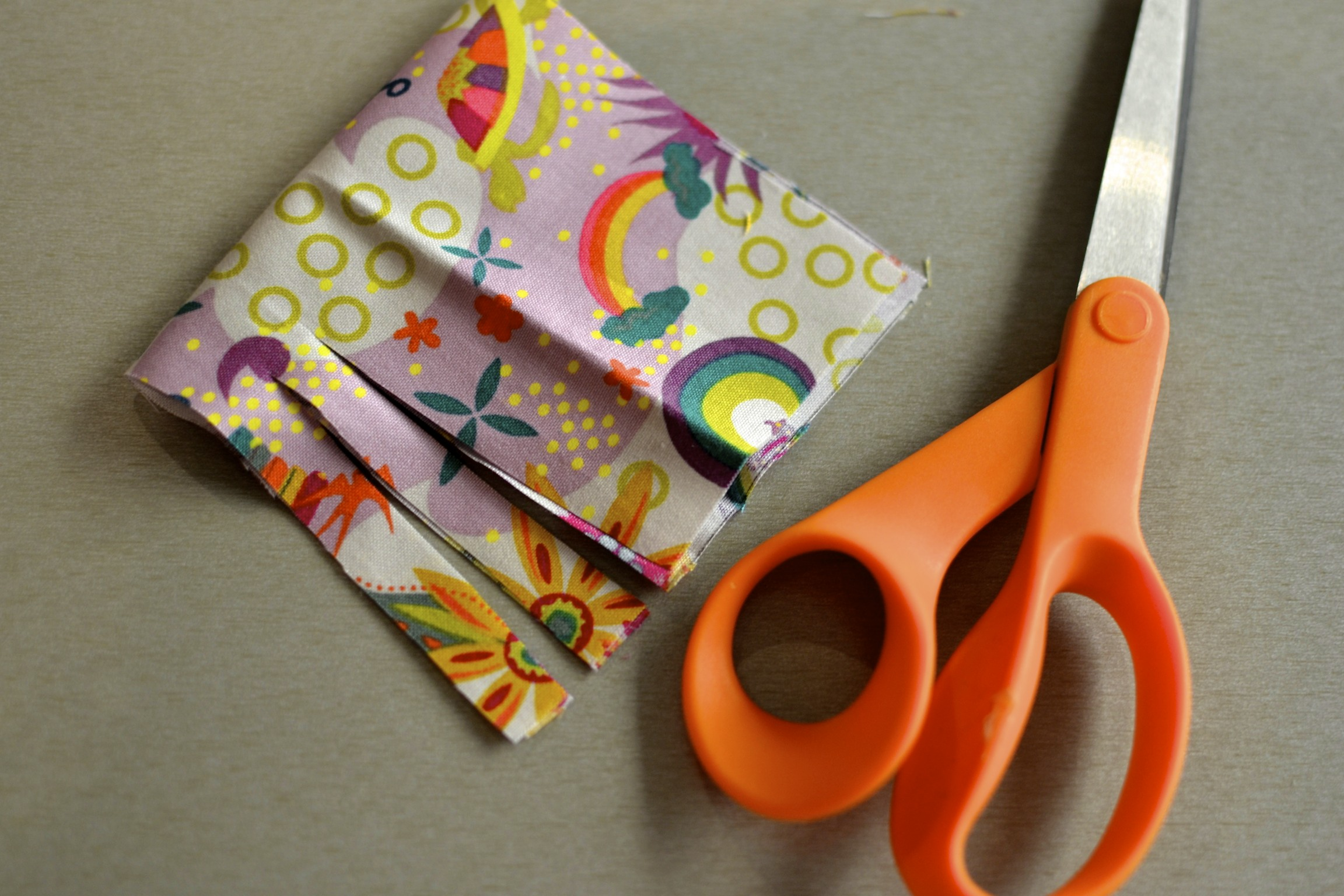 """cut small strips, about 1/2"""" wide. leave about 1/2"""" of fabric uncut at the fold in the fabric."""
