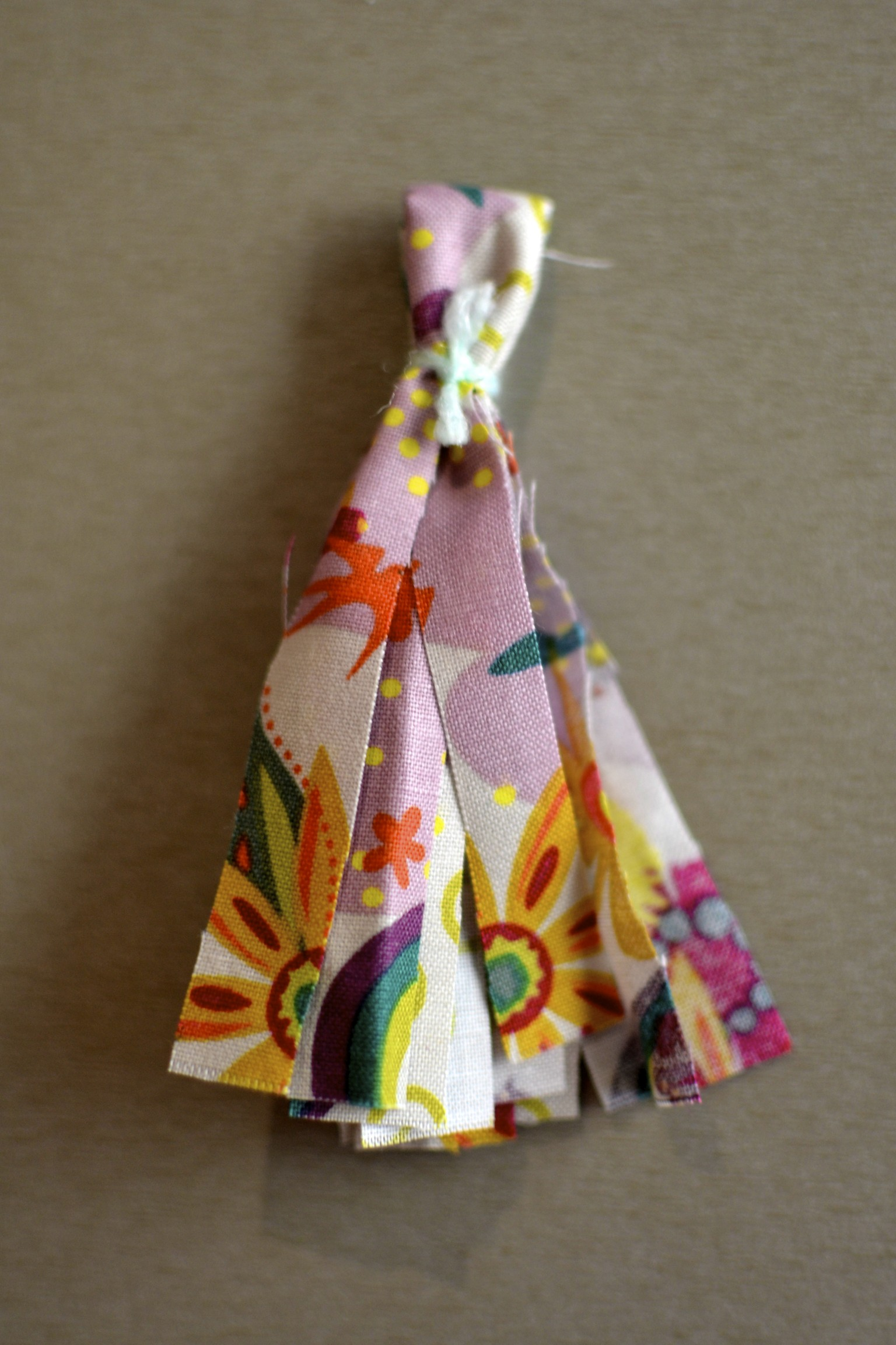 """tie the folded strip with ribbon, yarn or another strip of fabric. leave about 1/2"""" of a loop at the top."""