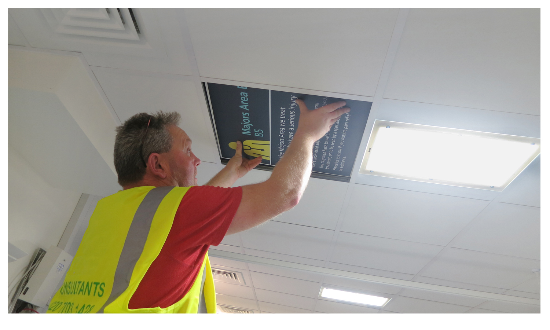 A team member installs a ceiling panel.