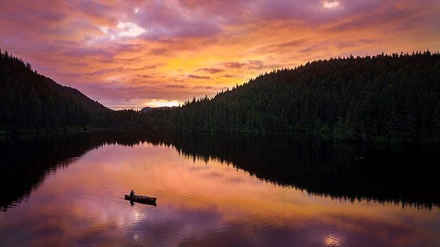 """Tutka Lake, AK @10PM.  After a boat ride and 30 minute hike in the forest to this location, I looked out at this reflection and thinking it would be a cooler shot, I said under my breath """"man, wish we had a canoe up here."""" My new friend and guide Karyn responded """"hang on, I think I have one stored around here."""" 15 min later she had unearthed this boat from deep in the forest and was cruising through the shallows of the lake in this canoe helping make this beautiful shot! Definitely didn't expect that but glad it worked out!  Shot with Mavic, edited w/ #iPadPro, #kerdowney experience."""