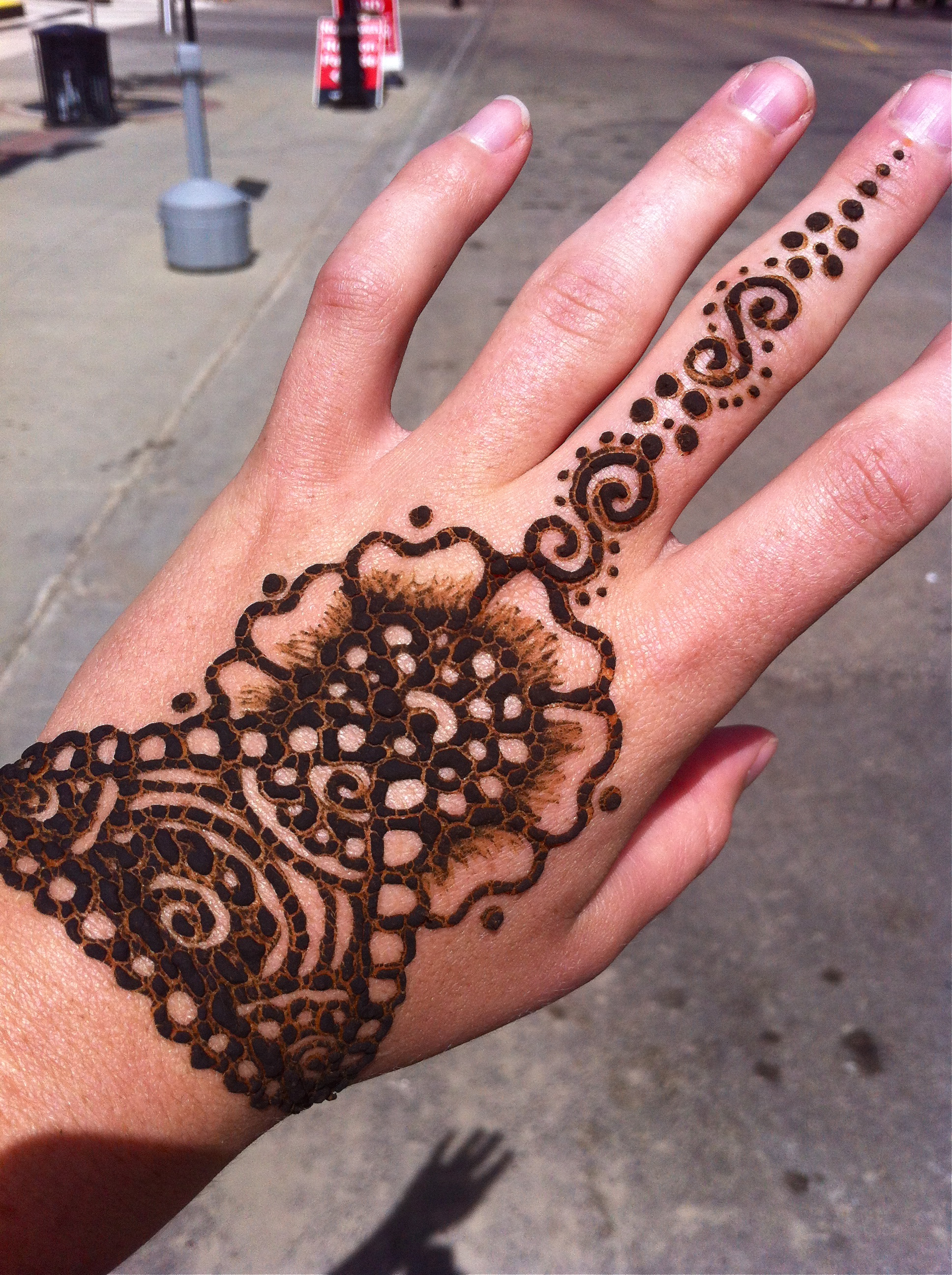 The henna paste goes on black, but dyes your skin a brownish-orange color if left on for at least 5-7 hours