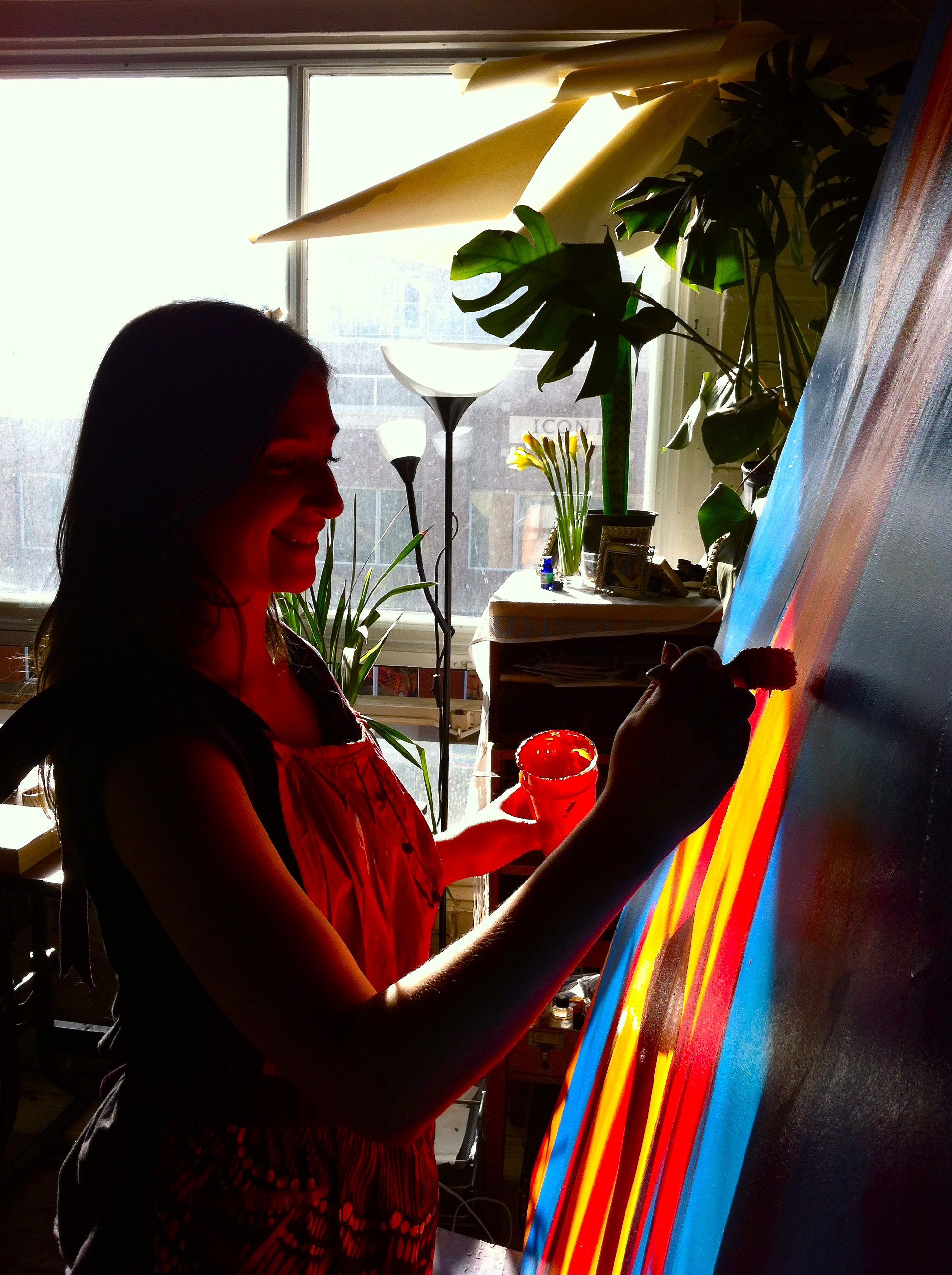Malorie painting in her sun-drenched studio