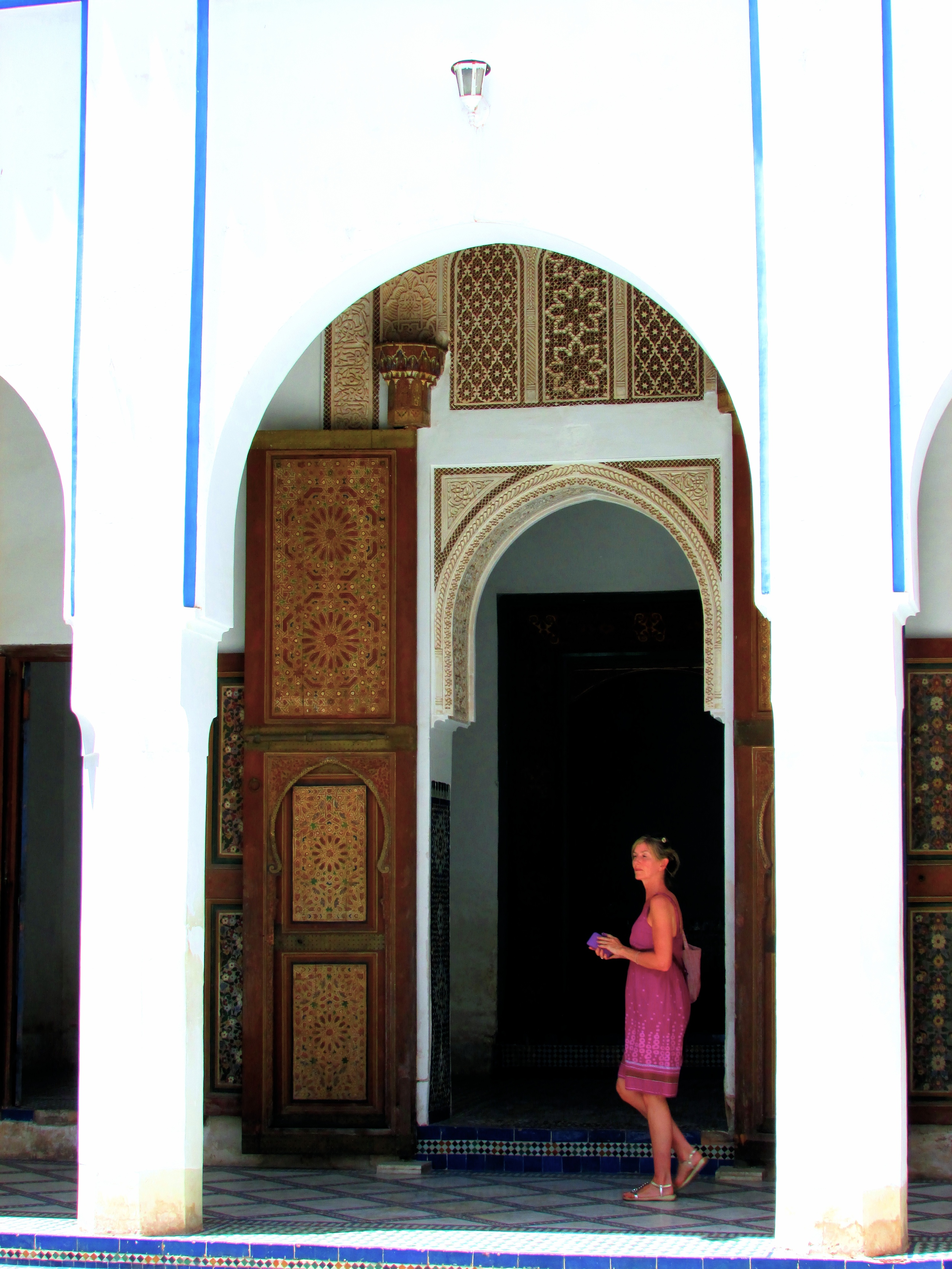 A fellow tourist enthralled with the tiles, painting and elaborate carving at a historic palace in Morocco