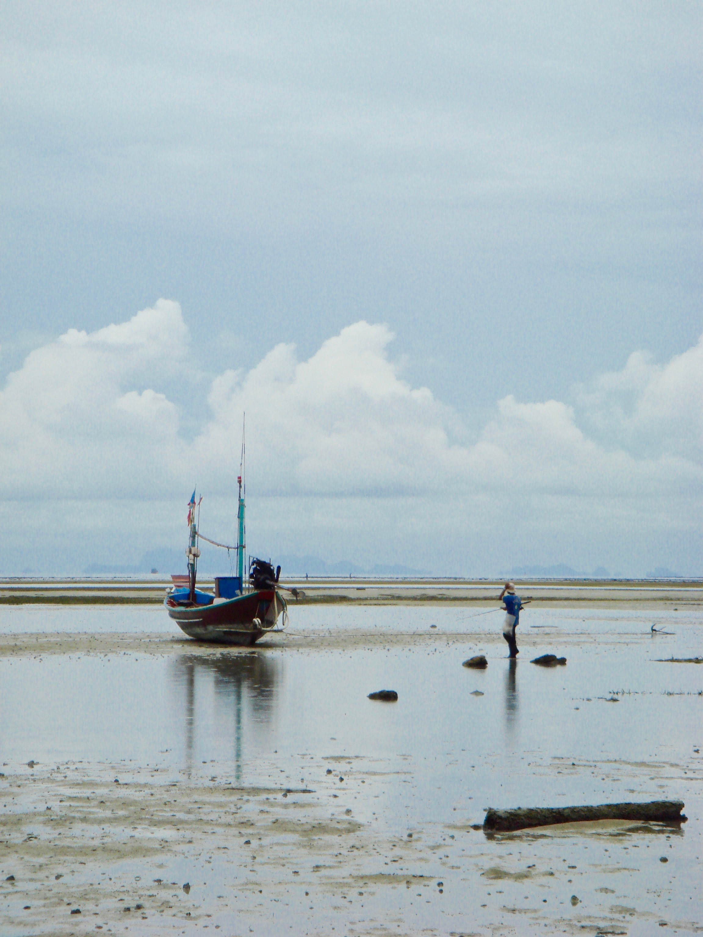 A fisherman and his boat at low tide on Ko Pha Ngan, Thailand