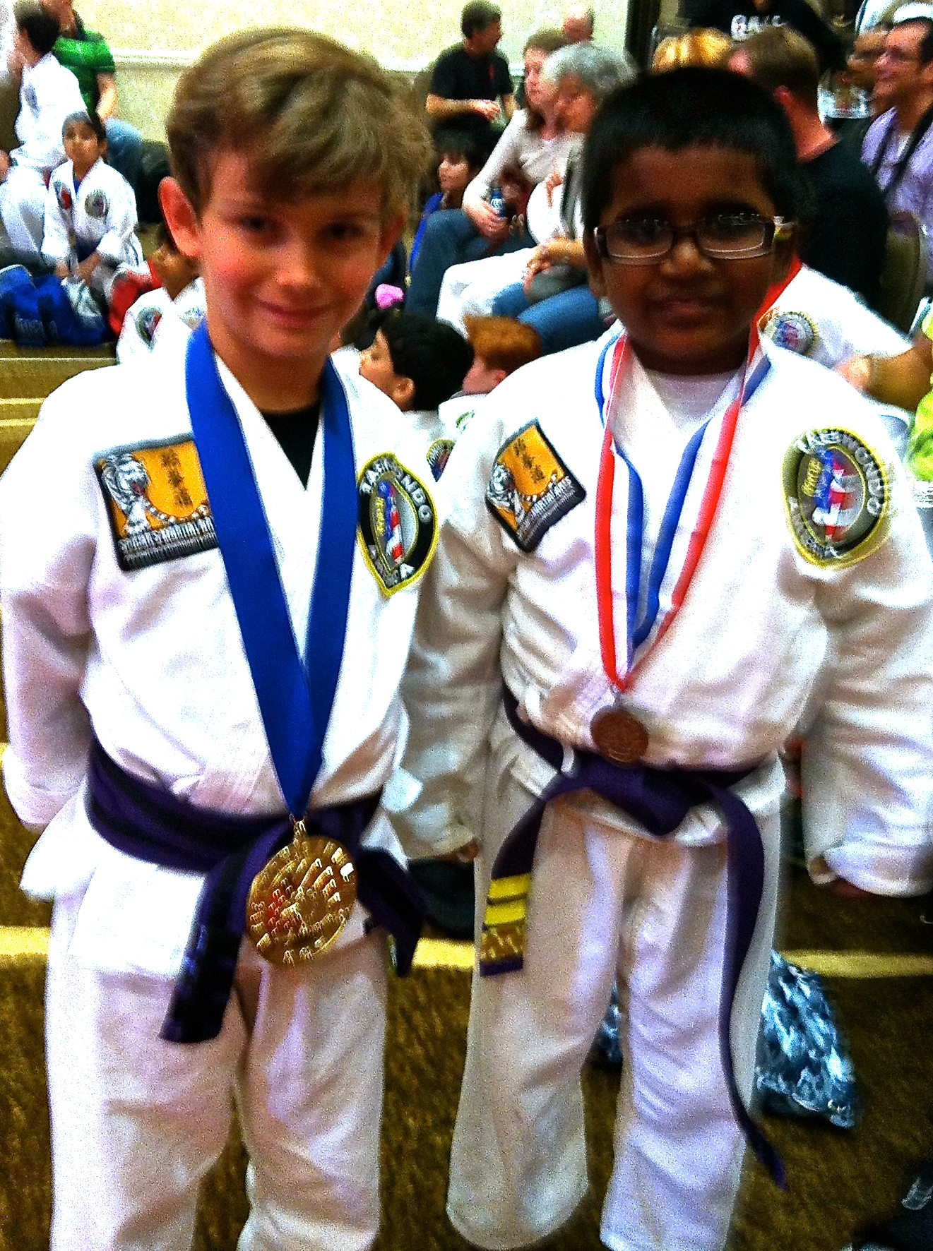 Jaxon Capps (left) winning gold medal in forms in the Purple Belt Junior division. Posing together with his friend Manasrishi Tummala.