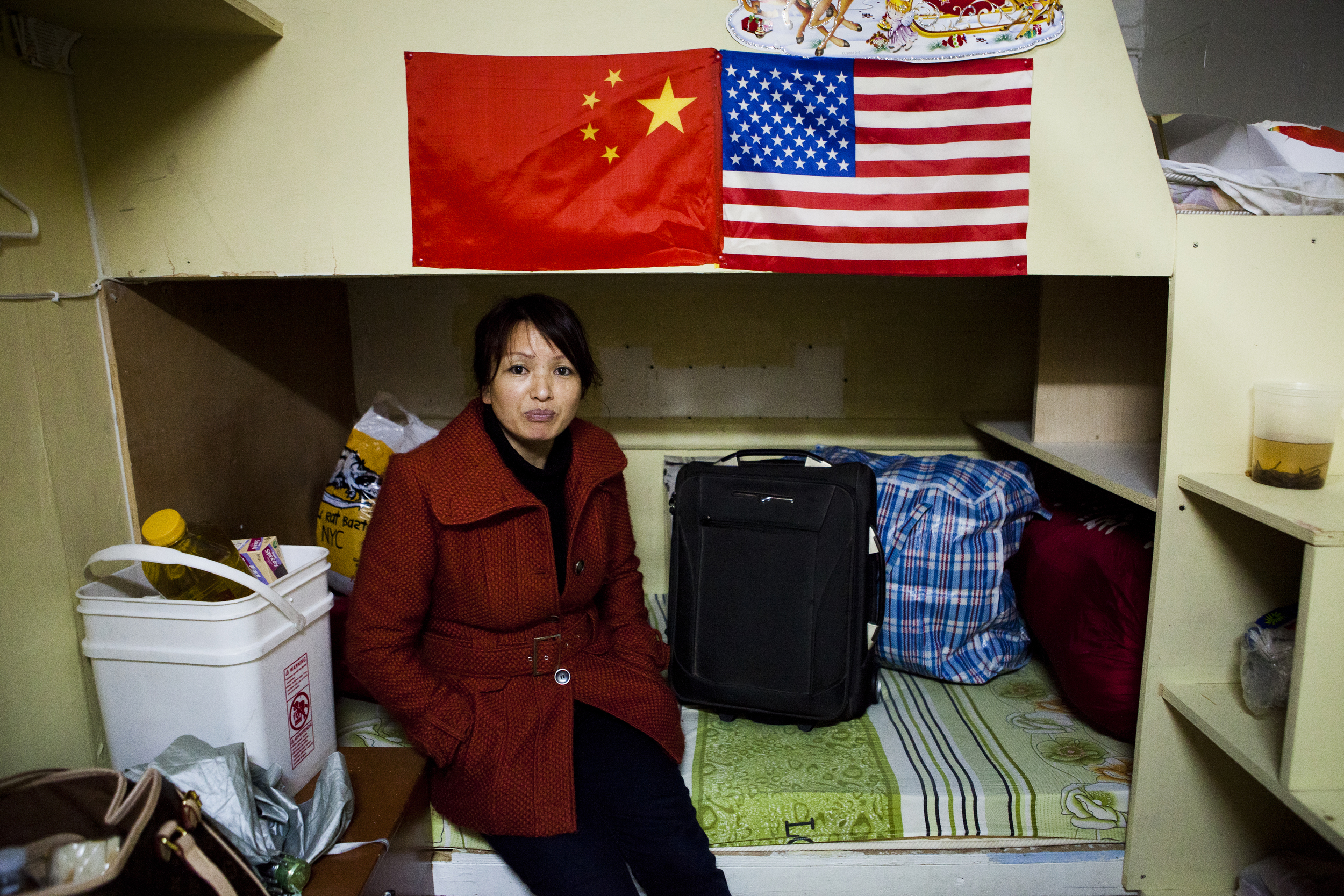 Chin Tu Yu in cubicle #6 at 81 Bowery packed a few possessions in the final minutes before vacating the building the evening of March 7th. Tu Yu Chin just arrived in US one month ago to join her husband who she hasn't seen in eight years. Chin currently works long hours at a laundromat in Chinatown. ©Annie Ling