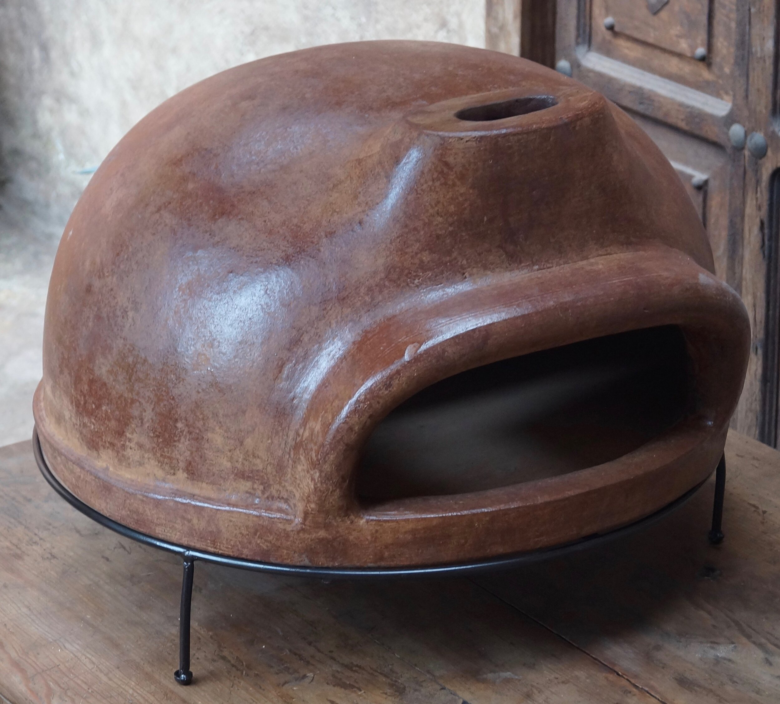 """Art. nr. 085BRY. Wood-fired stone pizza oven ø67cm with iron base and protective bag included. Packed in wooden crate - 4 per pallet 80x80x198cm  Wholesale price Ex-Netherlands: 130 Euro + VAT  Containerprice Mexico: USD 109 in 20ft (200pc) or USD 98 in 40""""HC (480pc).  Mix products in your pallet- or container order."""