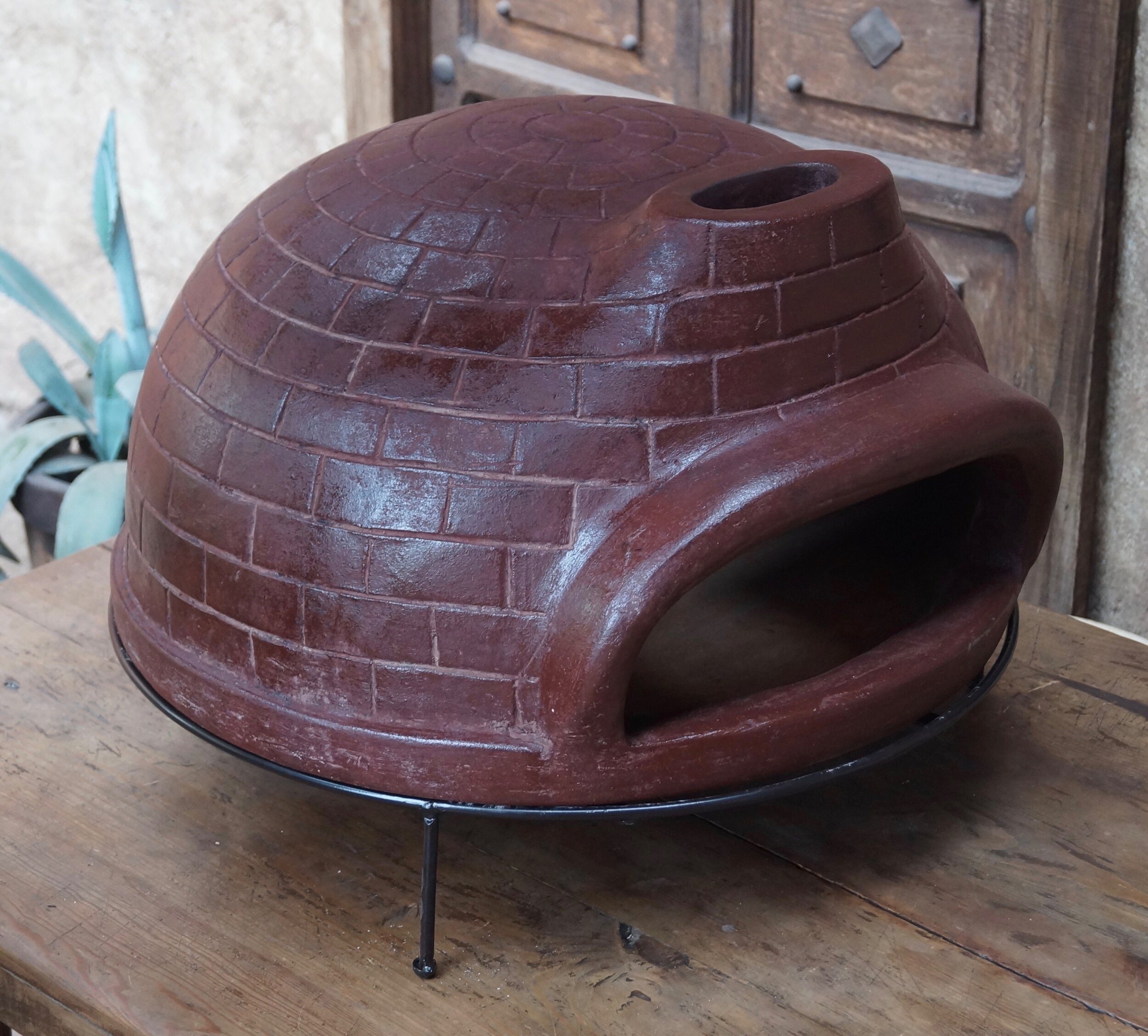 """Art. nr. 090RD. Wood-fired brick-design pizza oven ø67cm with iron base and protective bag included. Packed in wooden crate - 4 per pallet 80x80x198cm  Wholesale price Ex-Netherlands: 130 Euro + VAT  Containerprice Mexico: USD 109 in 20ft (200pc) or USD 98 in 40""""HC (480pc).  Mix products in your pallet- or container order."""