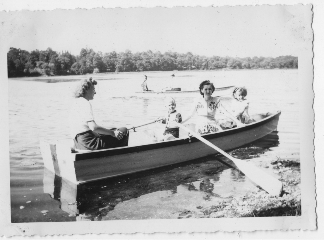 Family row boat excursion on a typical wooden resort boat of the era