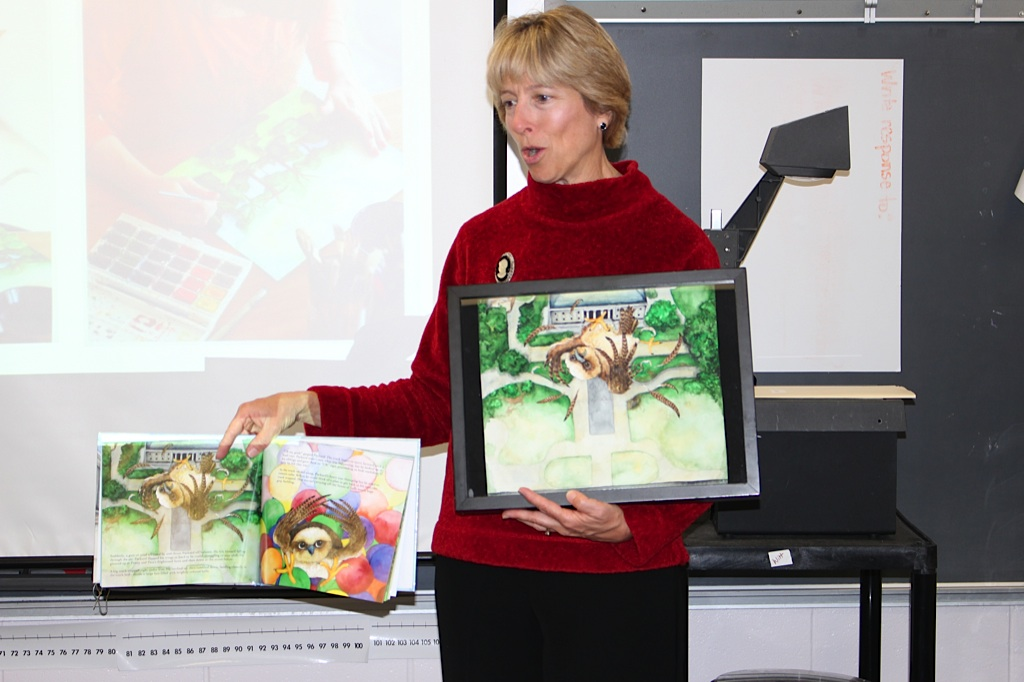 Susan Levine shows students one of the original paintings from Packard Takes Flight