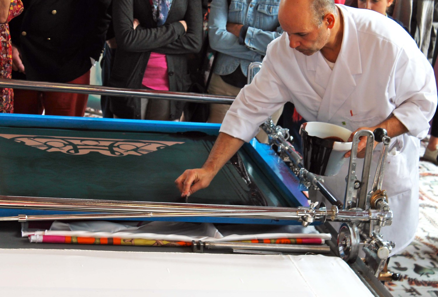 Preparing the screens for the layers of ink used on the scarves.