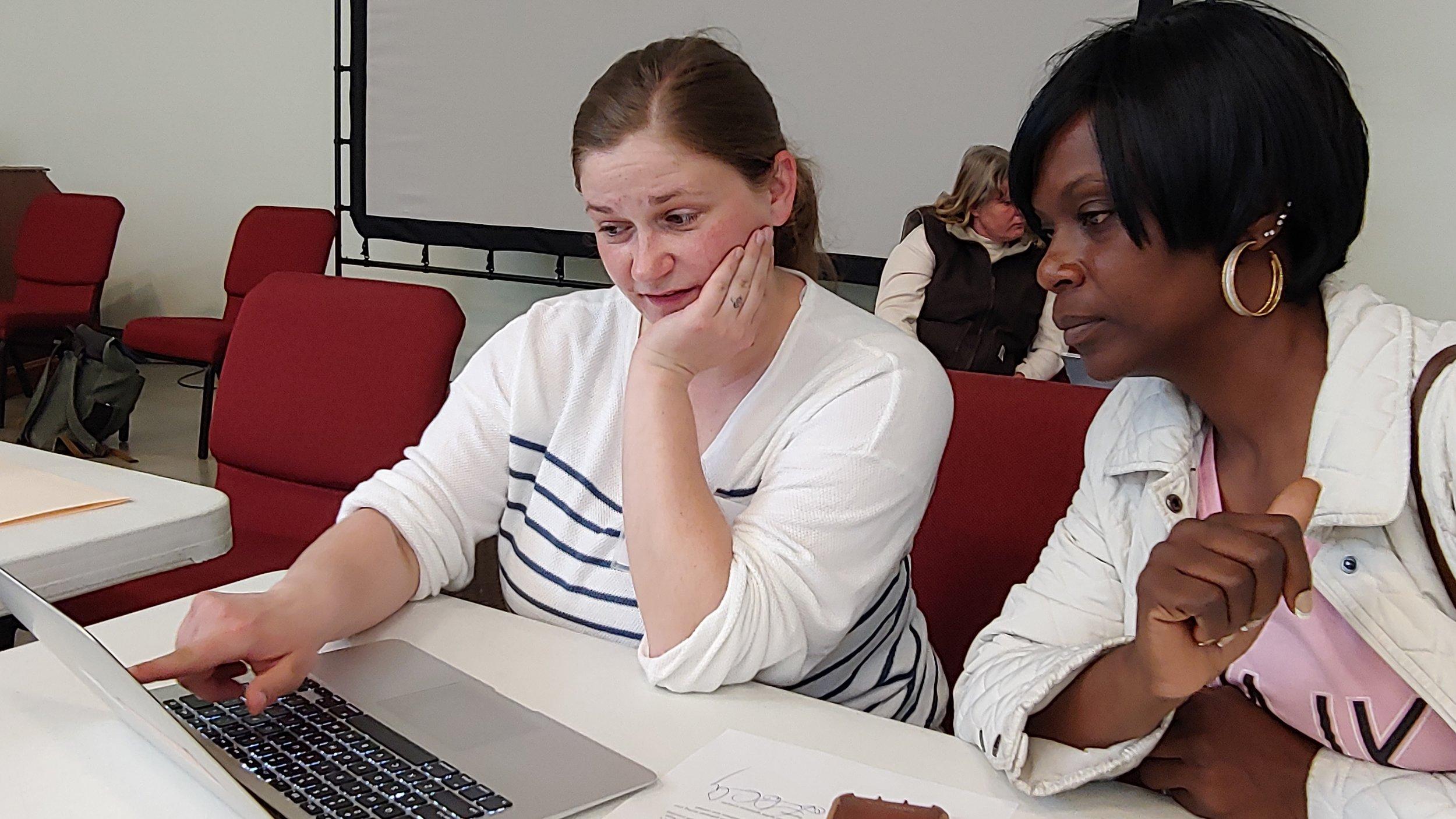 Volunteer UMKC student Beth Beavers consults with Tamara Sigars at the Expungement Day event April 27