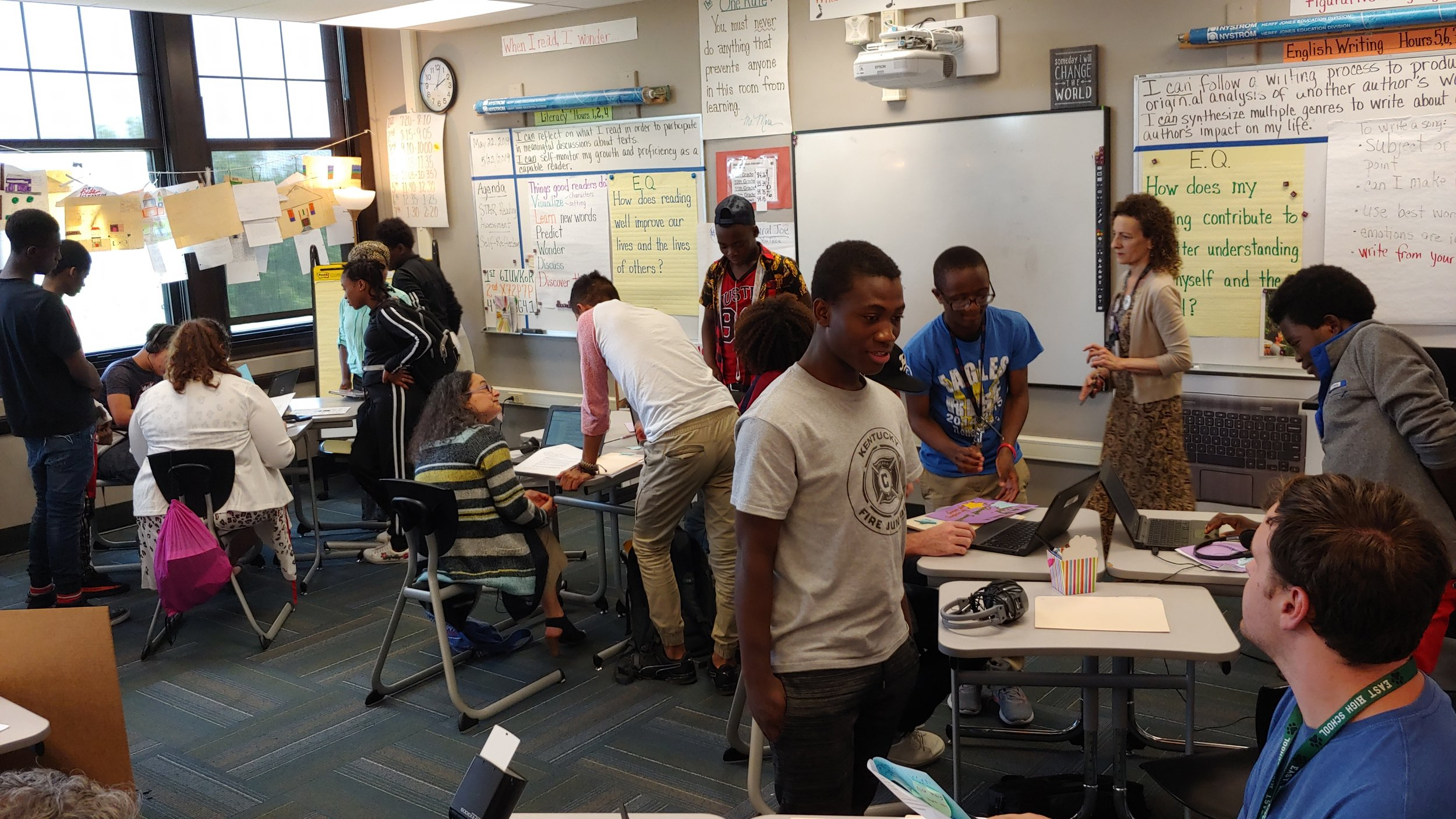 Visitors listen to East High School refugee and migrant students tell their life stories through music playlists.