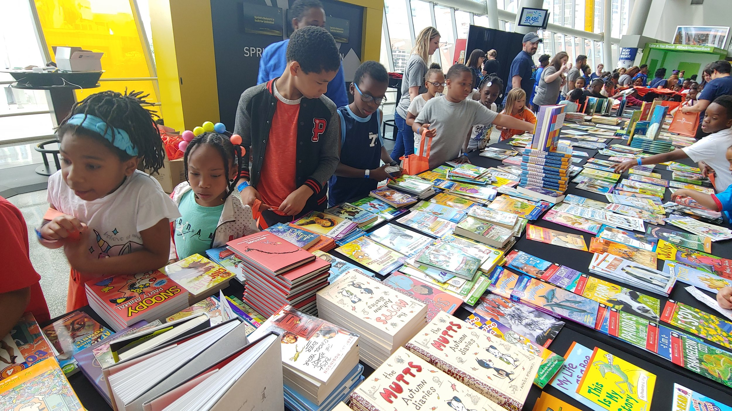 Children from LINC's summer program at Santa Fe Elementary School in Hickman Mills, including 7-year-old Za'Kirah in the blue headband, pick out books to take home at Turn the Page KC's Summer Reading Splash celebration at the Sprint Center June 19.