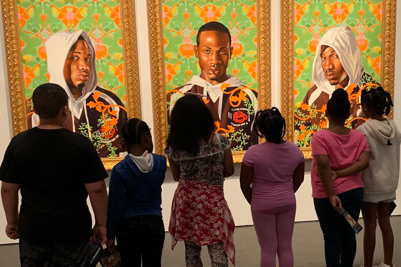 "Children from LINC's summer program at Wendell Phillips Elementary School study the Kehinde Wiley painting, ""Triple Portrait of Charles I,"" at the Nelson-Atkins Museum in Kansas City. Photo by Jamie Braden"
