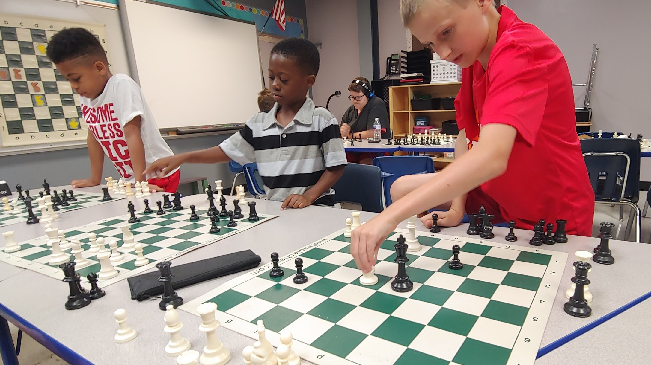 7-year-old Izaiah, center, practices his favorite moves at LINC's summer chess camp July 17 at Genesis School.