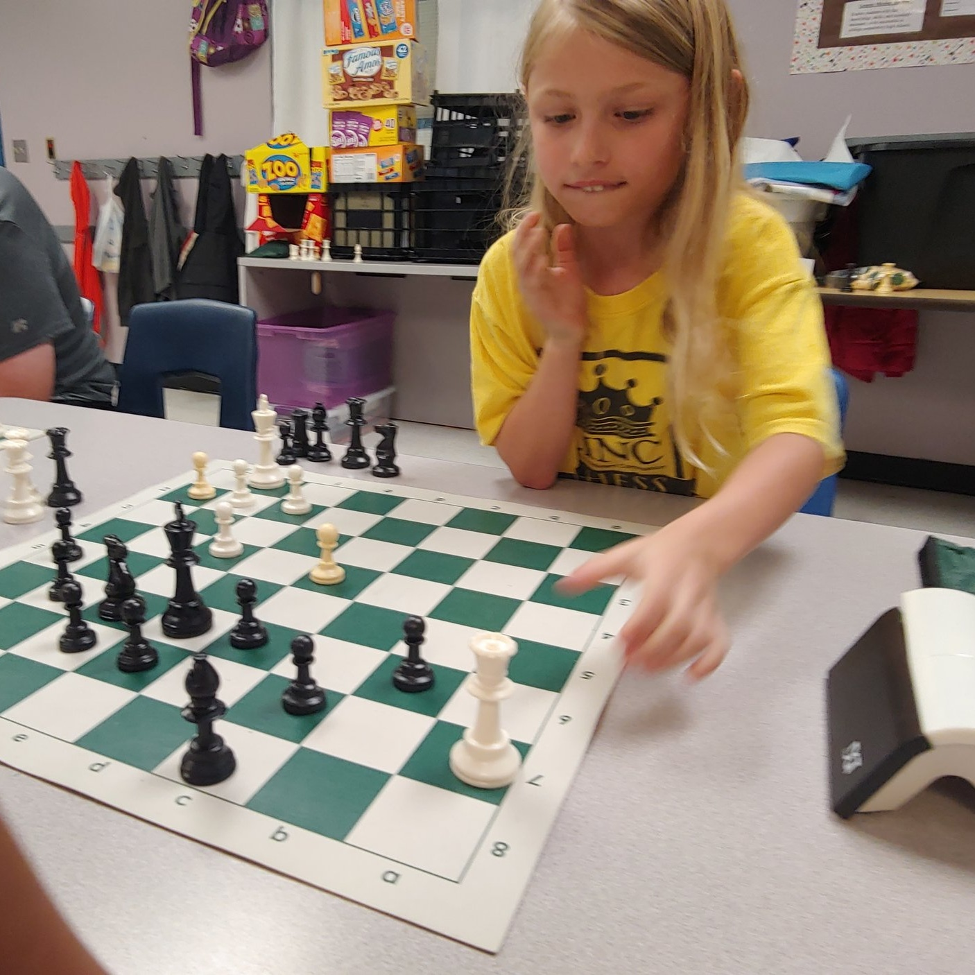 Kendall, 7, makes her next move at LINC's chess camp July 17.