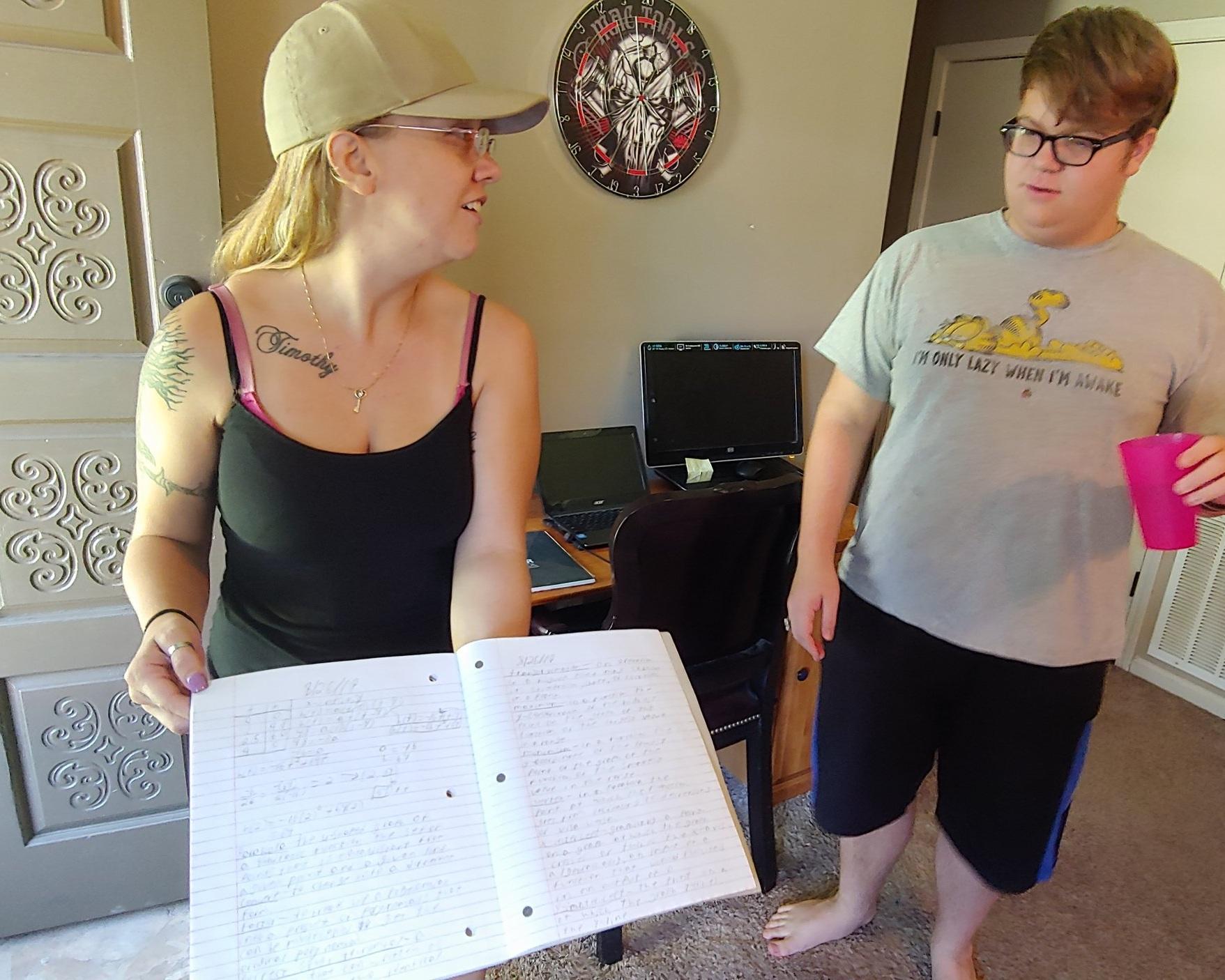 Kassie Argo looks over Adam's work in their Independence home