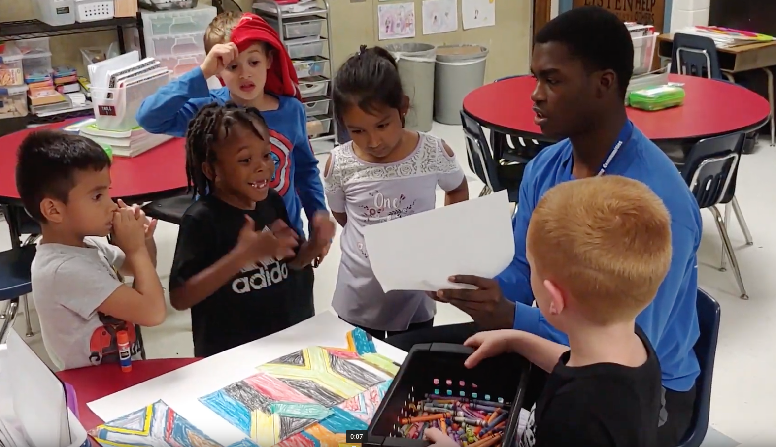 Children work on a collage based on South Africa's flag with LINC staffer Zion Triplett at Grandview's Meadowmere Elementary School.