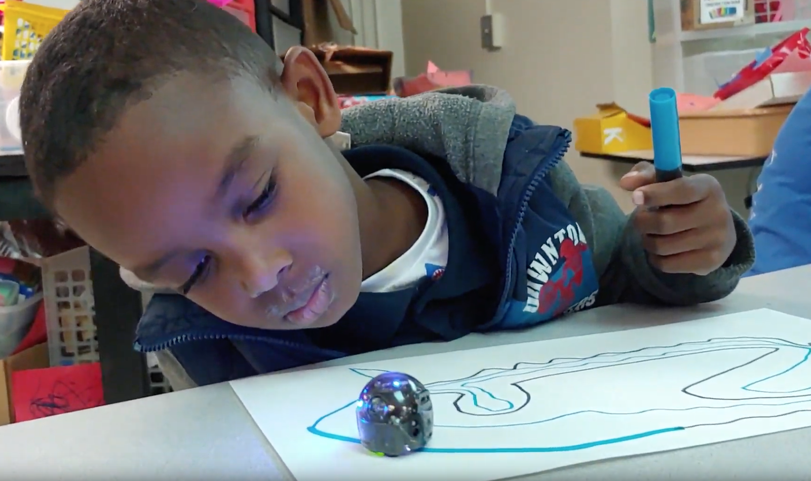 """Indian Creek kindergartner Roy """"RJ"""" Gonzalez Jr. watches a color-sensitive """"Ozobot"""" light up as it traces his drawing in a visiting STEM program by Urban TEC."""