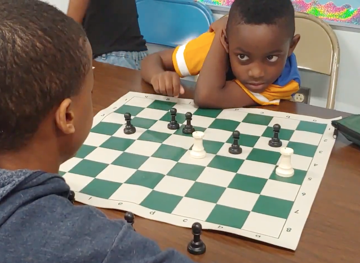 Braydon Allen, right, a second grader at Millennium at Santa Fe Elementary in Hickman Mills, watches for the next move by fifth-grader Peyten Thomas in a chess exercise called Rooks vs. Pawns.