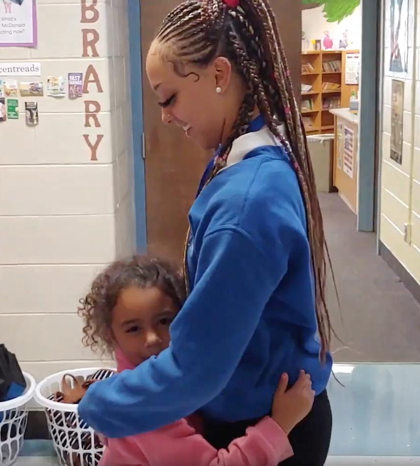 Meadowmere first-grader Aniya Carter shares a hug with LINC's Avaa Lofton