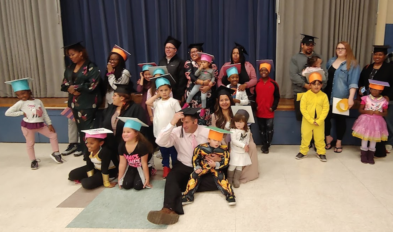Seven graduating families pose for a group picture as LINC's eight-week Families and Schools Together (FAST) program with the Fort Osage School District came to a close Oct. 22.
