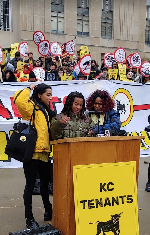 KC Tenants' Tara Rhaguveer, left, and Tiana Caldwell, right, stand alongside Caldwell's son, A.J. as he testifies at a rally at City Hall Oct. 30.