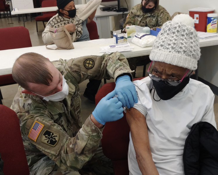 Sgt. Medic Jeromy Eslinger of the Missouri Army National Guard gives a Covid-19 vaccination to Opal Saunders of Kansas City at the Morning Star/LINC vaccination clinic.