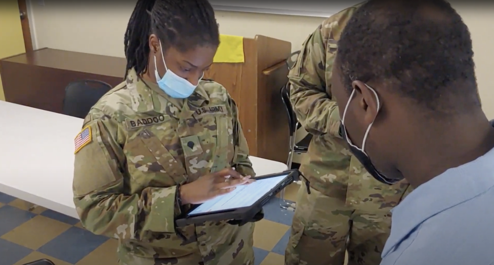 Missouri Army National Guard Specialist Crystal Baddoo prepares a client for vaccination in an Outbound team's visit to Guinotte Manor housing community in Kansas City.