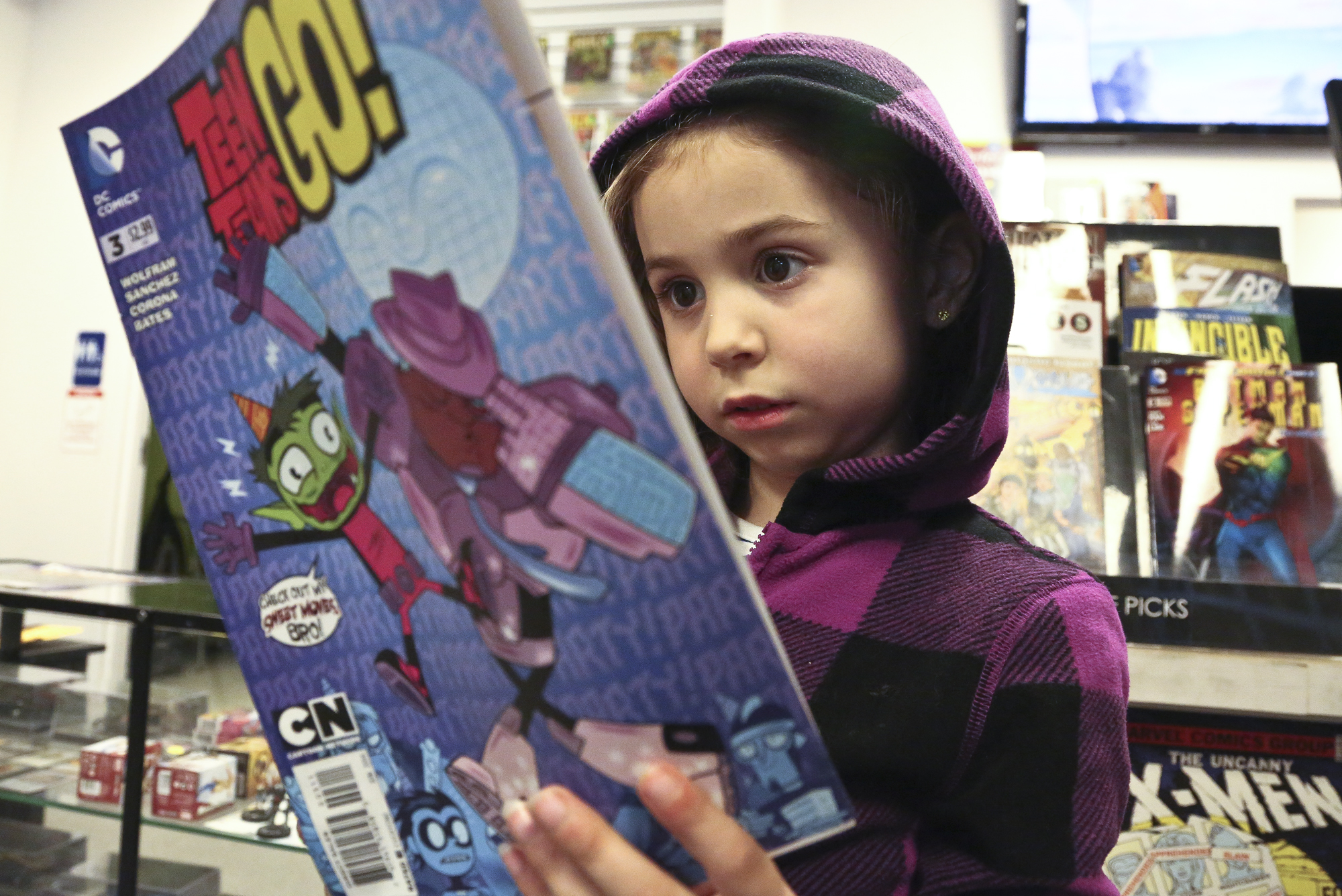 """Kylie Hunt, 6 reads the comic book """"Teen Titans Go!"""" as she waits for her father Bill Hunt of Felton to finalize his comic book purchases at Planet X Comics and Collectibles in York Township Friday, April 25, 2014. Kylie dressed up as a Bat Girl last year Bill said. Photo by Sonya Paclob"""