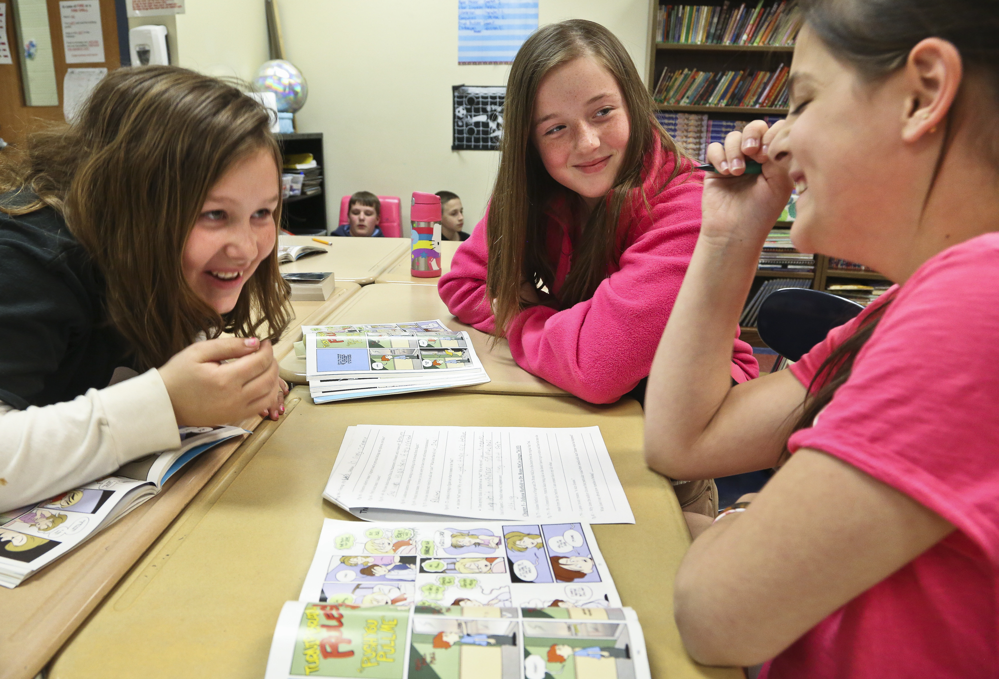 """Fifth grade students from left; Alissa Smith, 11, Anna Clemens, 11 and Lacie Kanely, 10 reviews the graphic novel """"Amelia Rules"""" in Ashley Ayres, communications arts teacher's classroom at South Eastern Middle School West, Fawn Township Monday, April, 28, 2014. Ayers and other teachers uses graphic novels is one of the teaching tools to get kids to read. Photo by Sonya Paclob"""