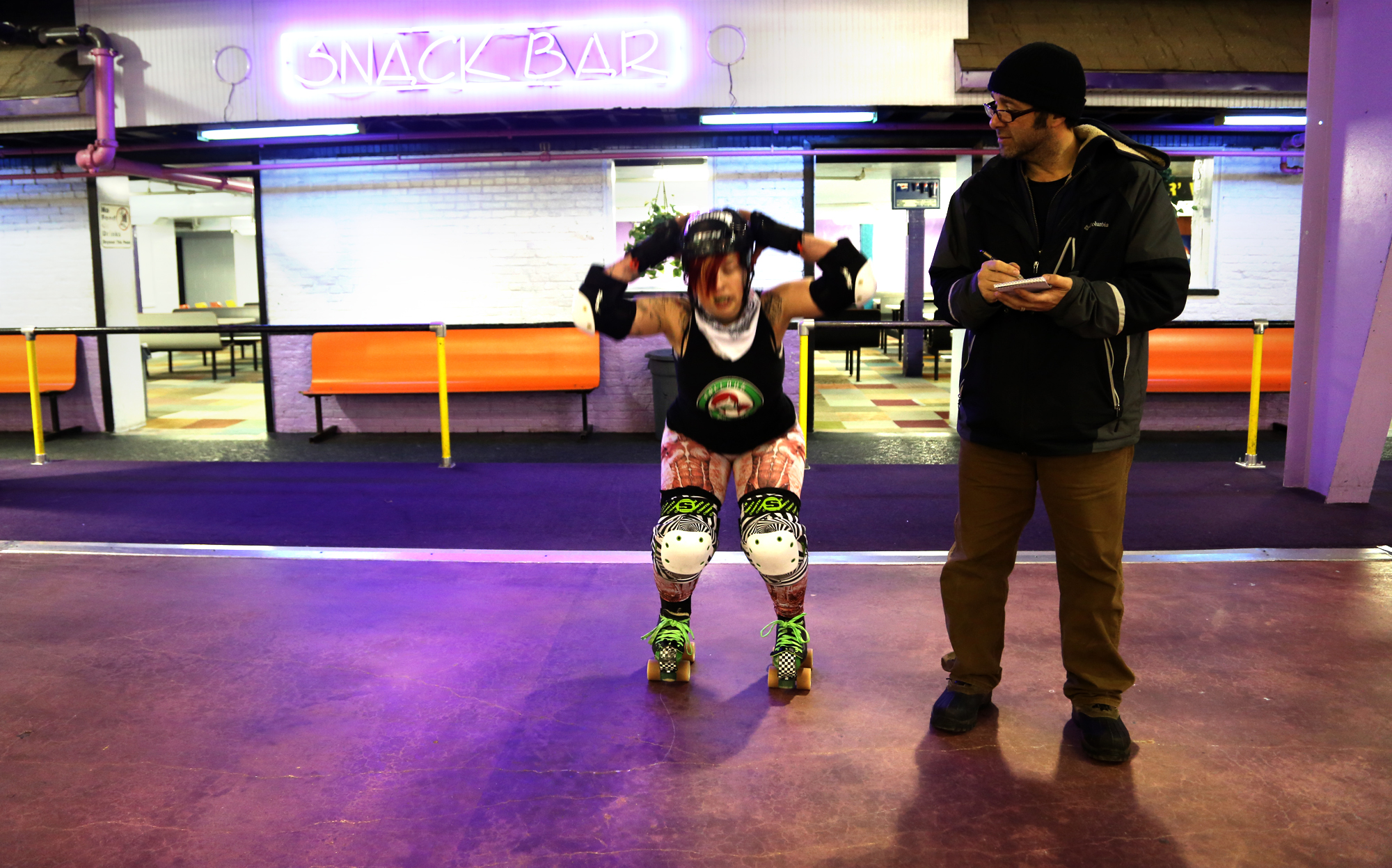 Jason Plotkin, York Daily Record photojournalist, takes notes do derby woman squatting in skates.