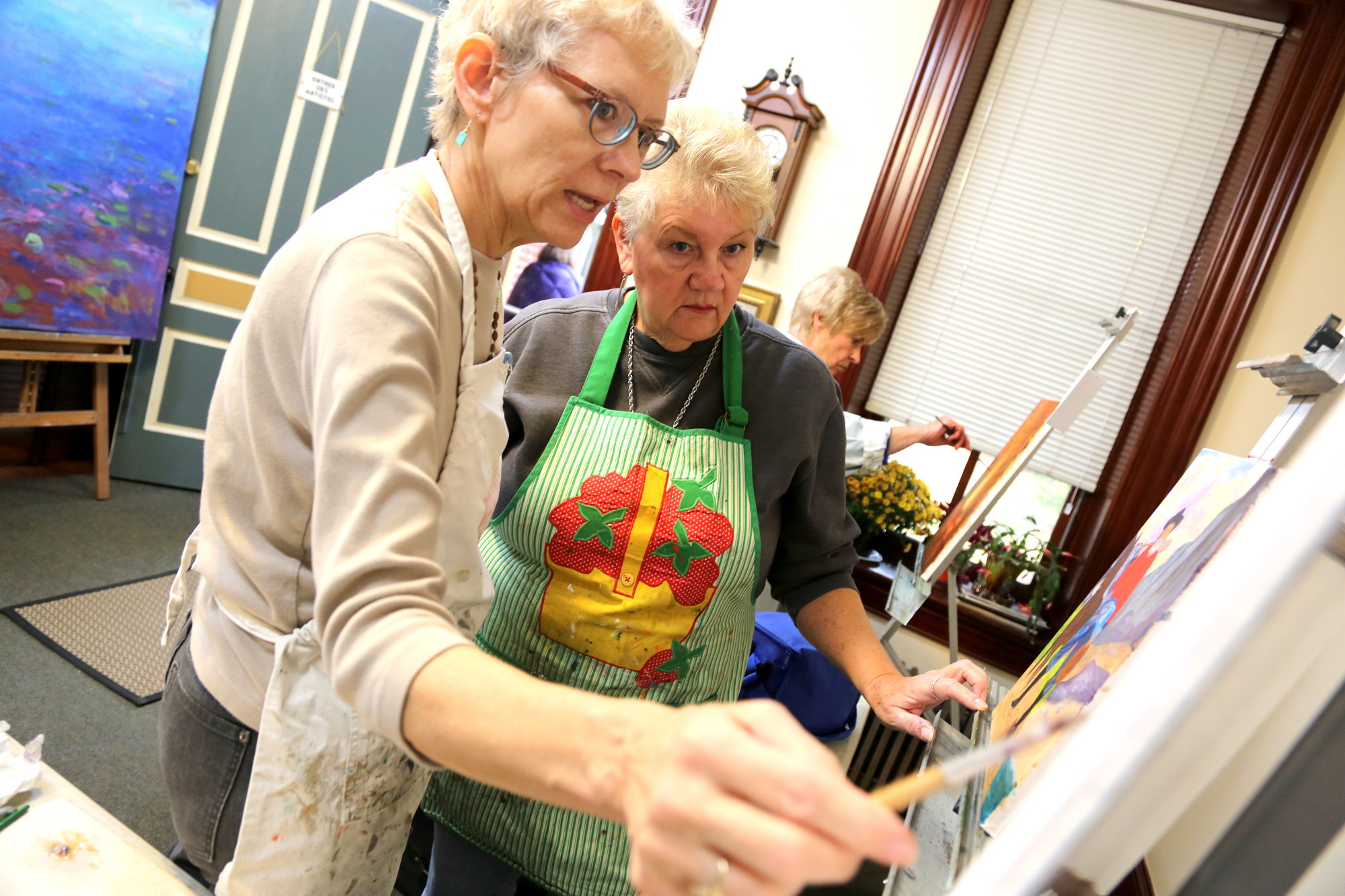 From left, painter and teacher Marion Stephenson helps with her Dover Township student Jewel Stough's painting in her home at 721 S. George St., York. Photo by Sonya Paclob