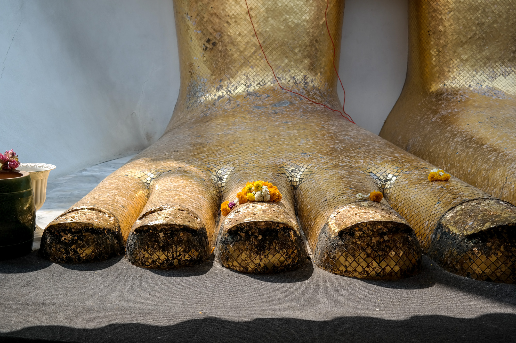 Foot of the 32 meter tall Luang Pho Tho statue (Standing Buddha) at the Wat Intharawihan, a buddhist temple.