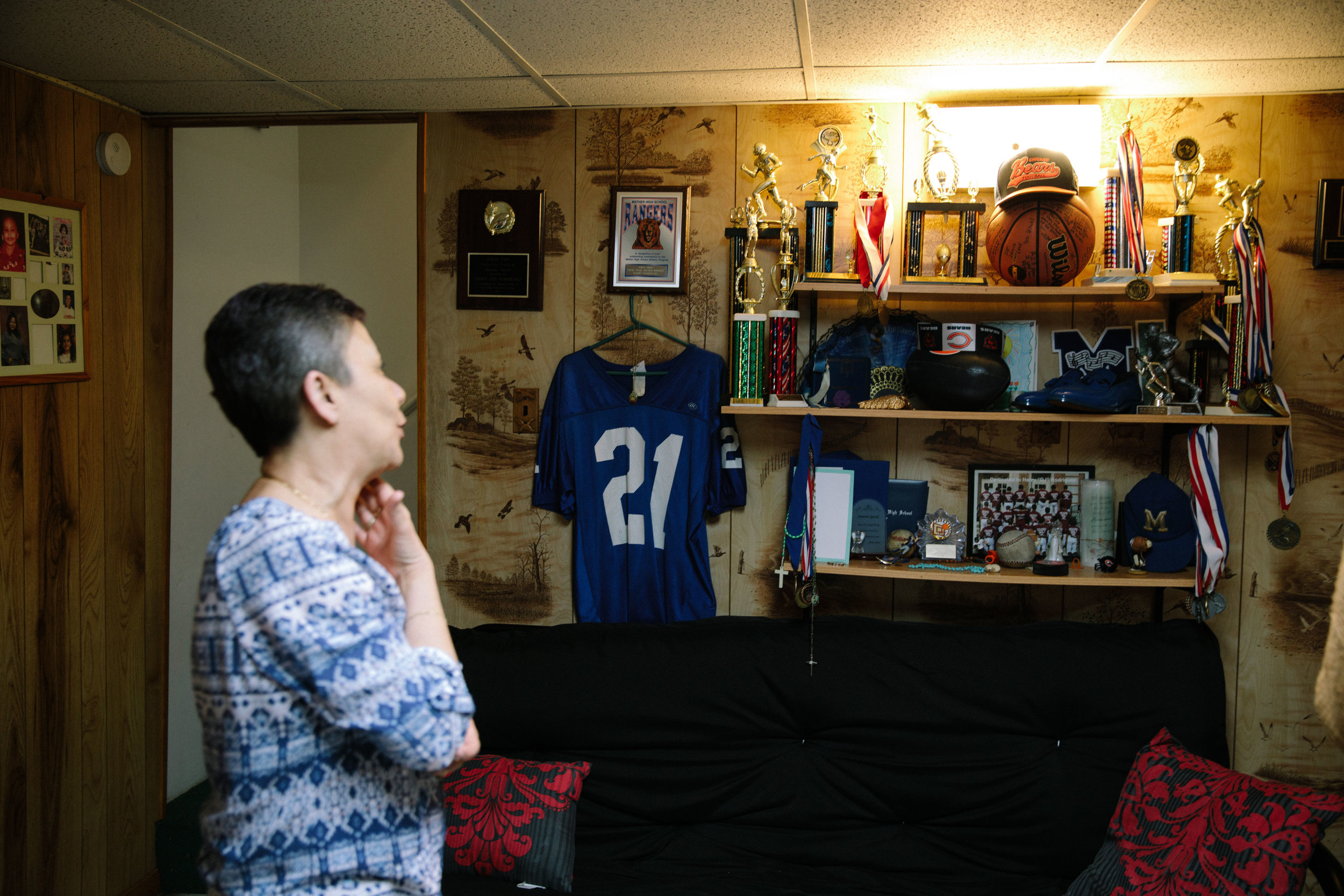 Elizabeth Ramirez, stands in the basement of her home gazing at a wall of rememberence devoted to her late son Dee Jay. The shelves contain momentos of Dee Jay's life and death, with items like his high school diploma, sports trophies, and the program from his memorial service. Dee Jay was shot and killed in the Belmont-Cragin neighborhood of Chicago in 2011. Dee Jay's mother, Elizabeth, helped found an organization called Parents for Peace and Justice to help provide support and advocacy for families who have also lost children to gun violence in Chicago. MCC has partnered with Parents for Peace and Justice to help support them in their important work.