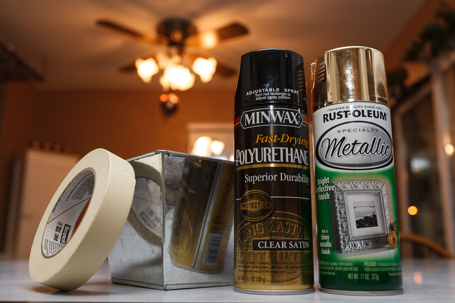 """Supplies needed: 1"""" masking tape, silver tin flower pot with liner, gold spray paint, and clear satin polyurethane."""