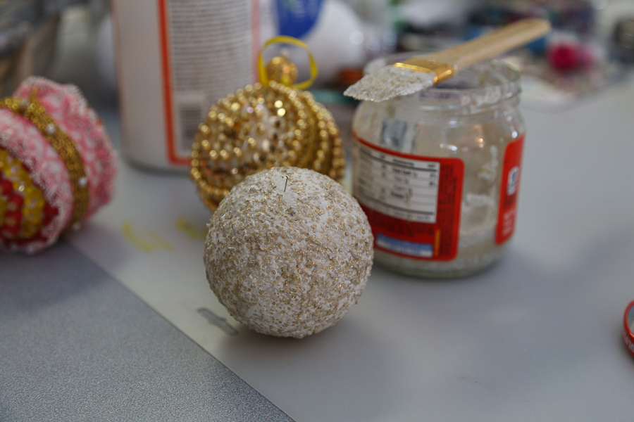 Here you can see we mixed a gold glitter with Mod Podge and painted the whole ball.