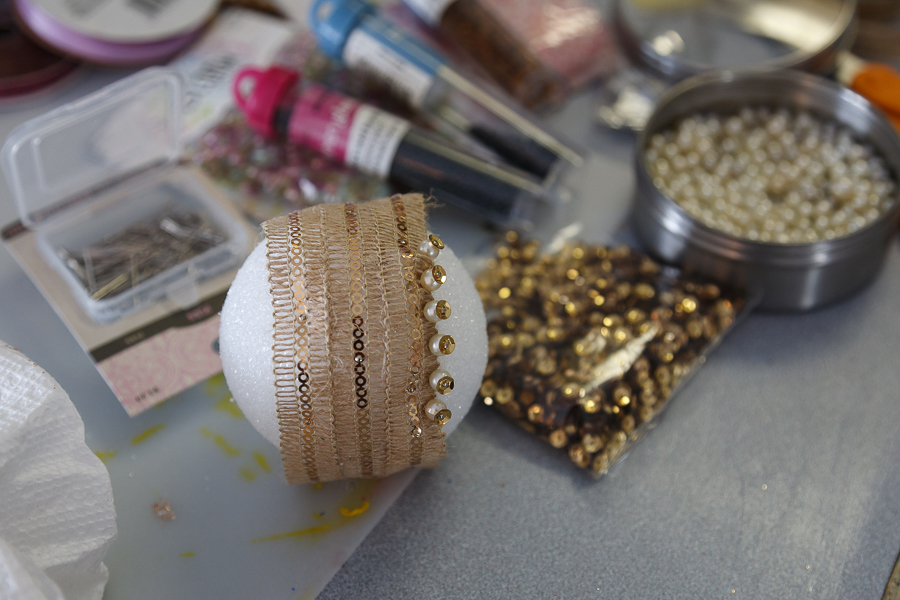 Here's one of my ornaments in the beginning phase. Three pieces of ribbon wrapped around. I then secured the edges on both sides by using a gold sequin, pearl bead a push pin. I eyeballed it to evenly space the pins.