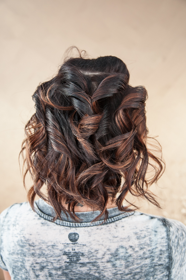 Start by adding  flatiron ribbon curls  to the hair, turn the flatiron up as you go. When doing these curls, start at the nape of the neck and clip the rest of the hair out of the way. Take 2inx2in sections and work your way up. Use  Aquage Working Spray  with the flatiron to hold in the curls.