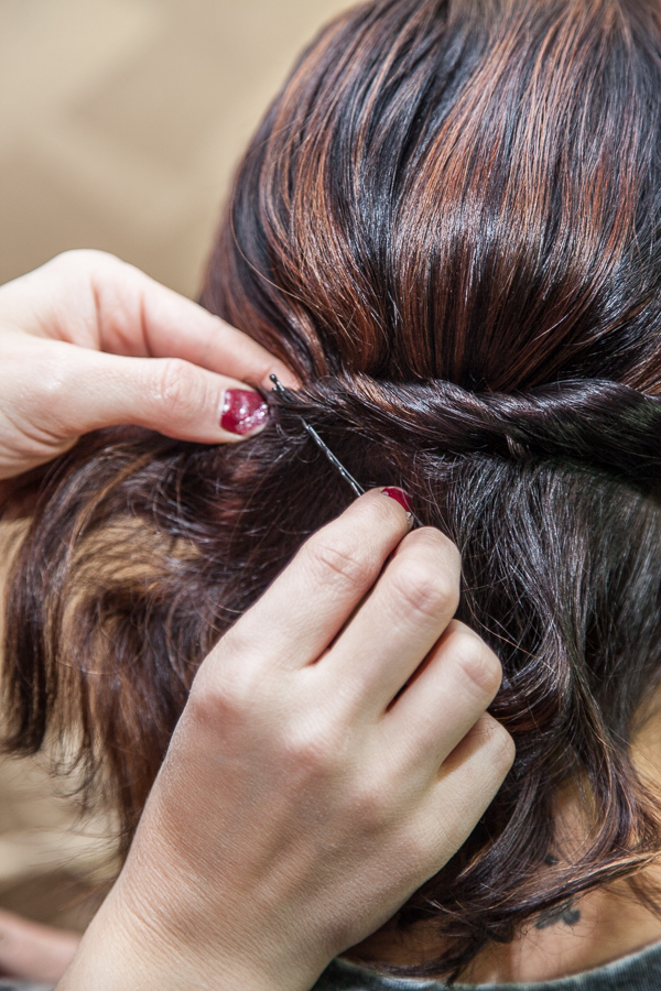 When you finish twisting at the other side of the head, take a bobby pin, without opening it, and slide it through the bottom part of the twist.