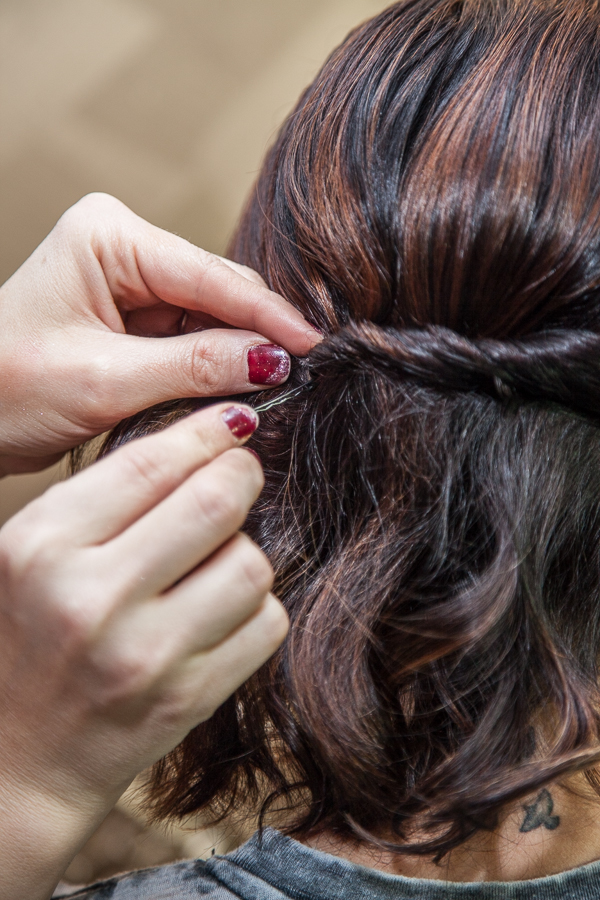 Take another bobby pin through another section of the twist and press it in and up at the opposite angle of the first one.