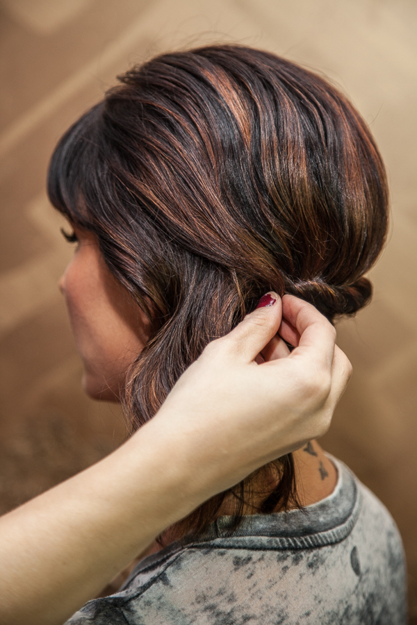 With a bobby pin, organically grab a small section of hair from the front to cover up the bobby pins in the back and blend the front section with the back. Push the pin into the X you made with the other two bobby pins and turn the pin towards the face to lock it in.