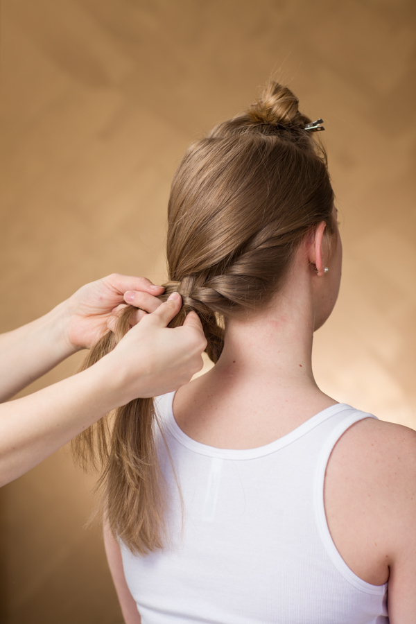 Leave a section out at the bottom to create another fishtail braid. When you create this braid, you will start on the left side of the head, only add from the bottom side of the braid. Be sure to direct it towards the front to join the other braid. Clip those two braids temporarily at the bottom.