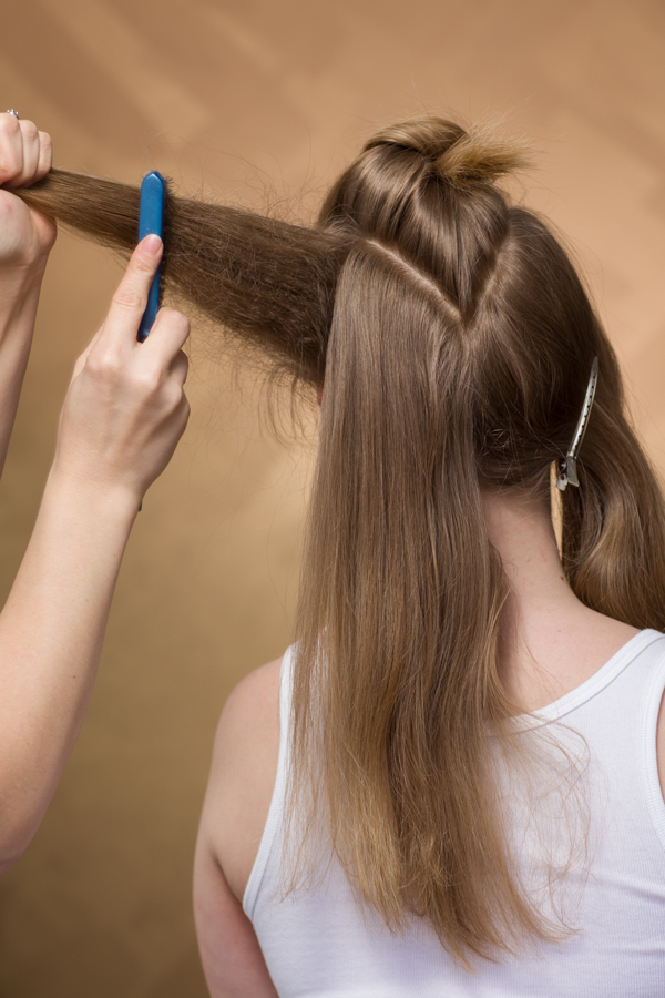 Create three sections. Backcomb one of the back sections from the front to the center back using an Aquage Detailing Brush and Biomega Firm & Fabulous hairspray.