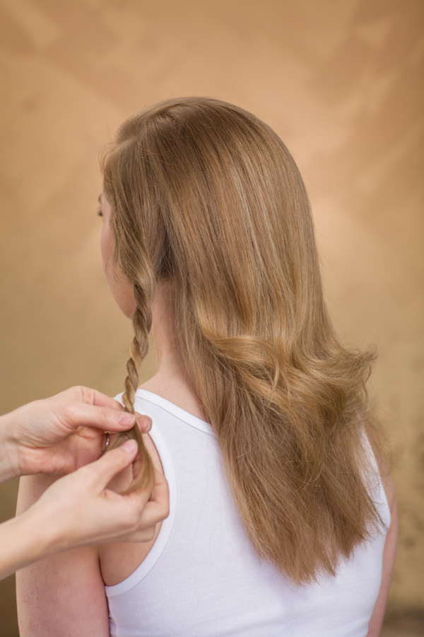 Backcomb and brush the top of the hair into place. Part a small section starting on the side of the head with the least amount of hair. Subdivide that section into two and twist the two sections together loosely to the ends.