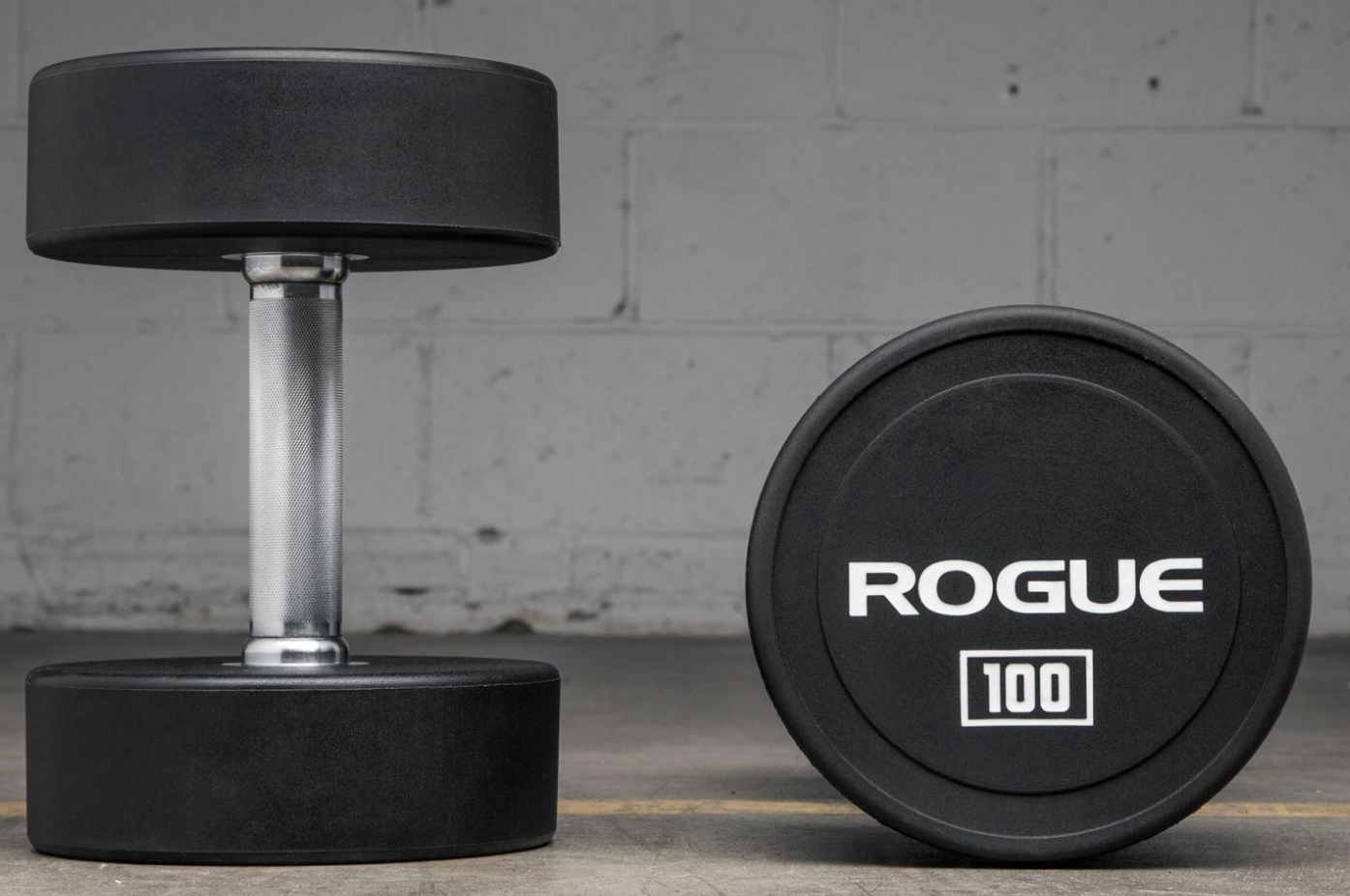 """Rogue Urethane Dumbbells - Sold in pairs and available in 5LB increments up to 150LB. As an alternative to traditional rubberized bells, this design features solid steel heads with a durable, shock-absorbent urethane plating, fully over-molded to the center. The heads are welded to a 6"""" straight hardened chrome handle to create a solid, single-piece dumbbell that moves fluidly and compactly and won't damage your flooring on a drop. Weight Increments: 5LB – 150LBEach precision-machined handle on Rogue's Urethane Dumbbells is the same 6"""" in length and includes a medium-grade knurling for a firm but comfortable grip. The handle diameter is 31mm for bells up to 45LB and 34mm for bells 50LB and up.The dumbbell heads vary in diameter from 127mm (for 5-15LB sizes) up to 204mm for bells 130LB and up. Each is finished in a distinct black matte with bright, clear increment markings and the Rogue logo in grey print. The combination of the urethane plating and textured finish makes these dumbbells uniquely low-maintenance, looking like new even after long periods of use."""
