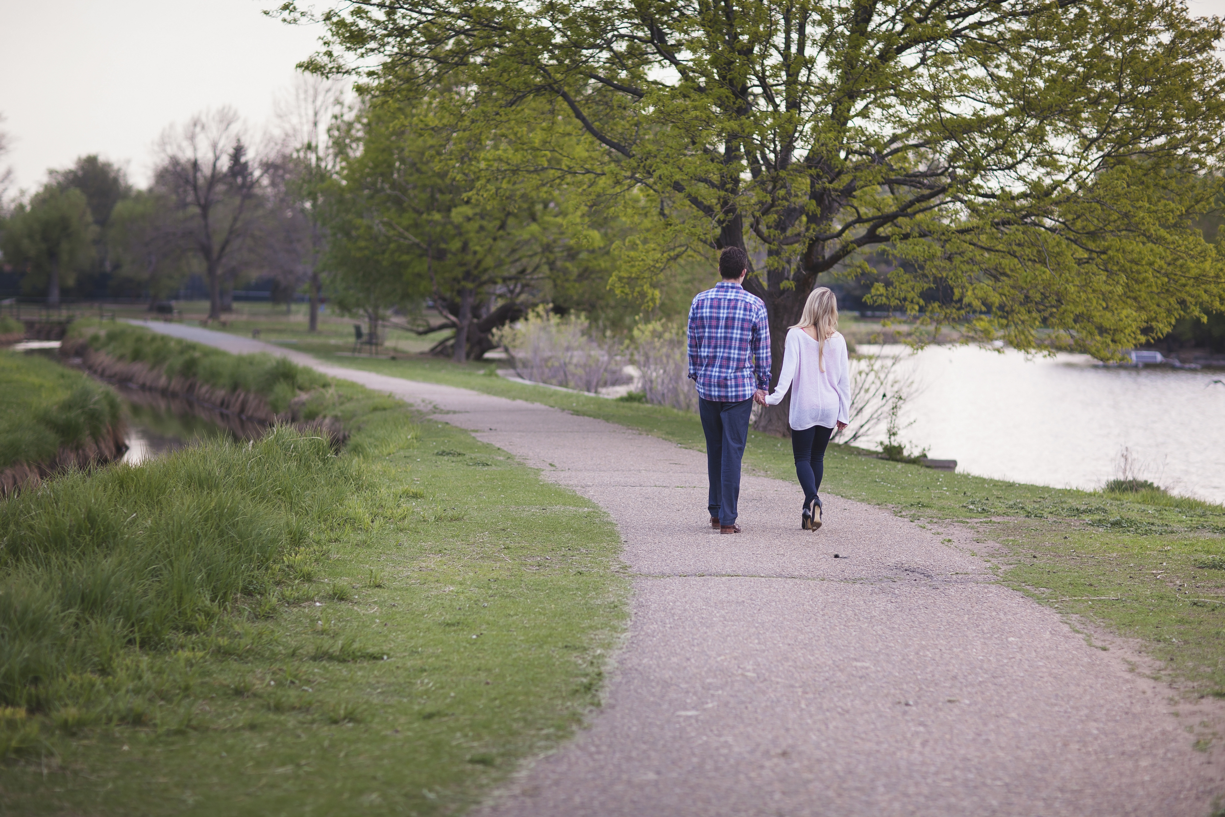 Denver Colorado engagement photography session with couple walking away on path hand in hand