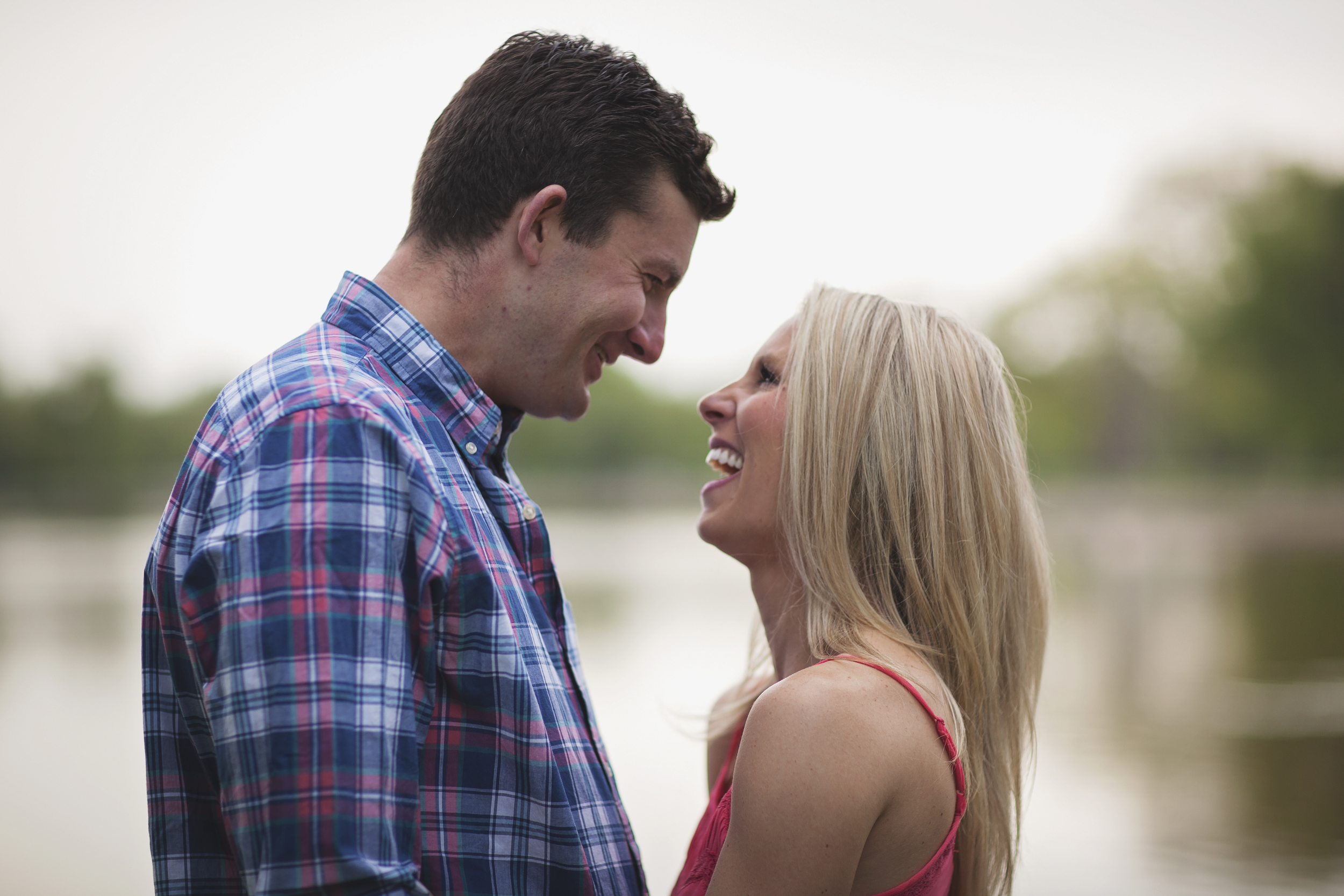 Engaged couple laughing in portrait with trees and lake blurred in background