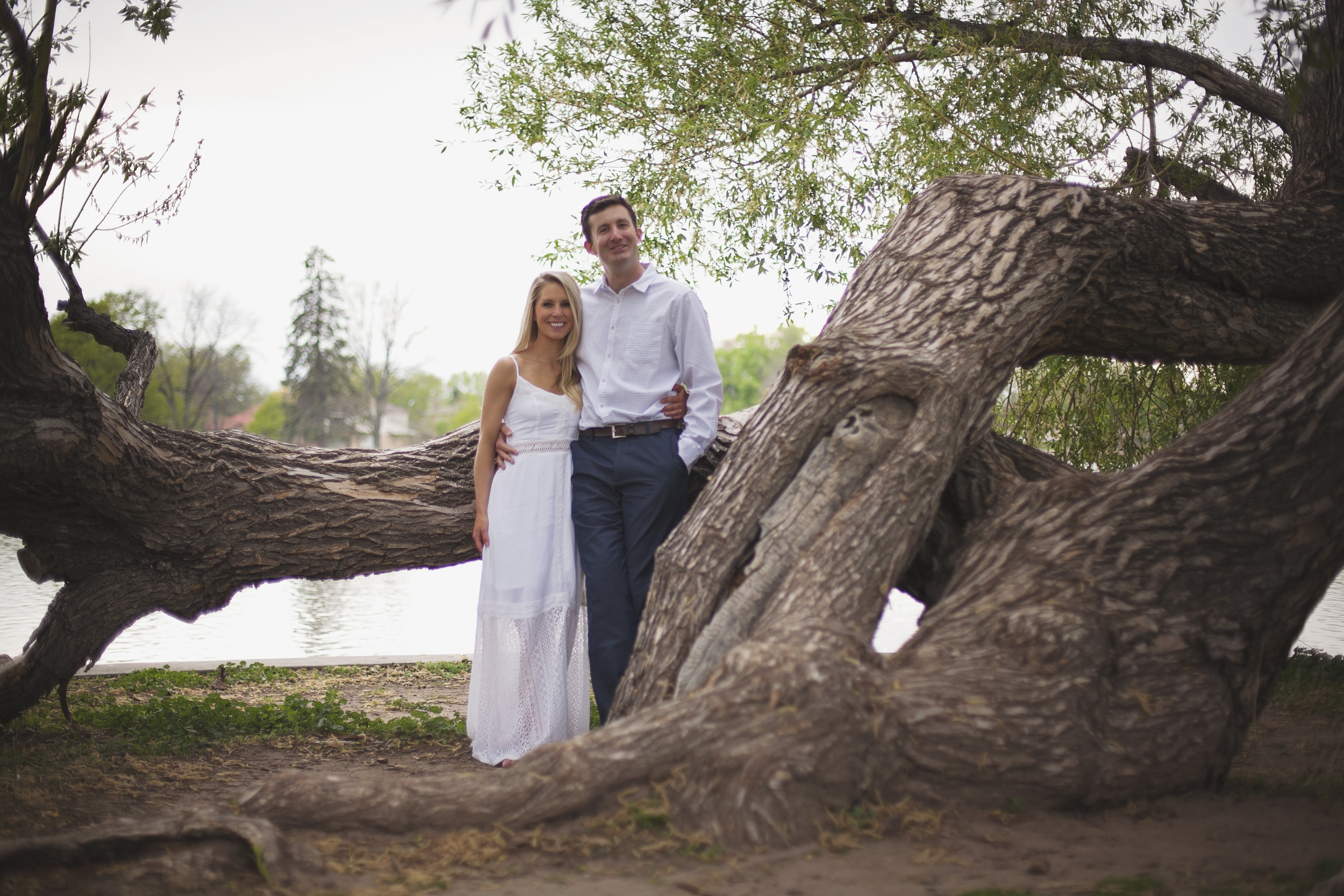 Couple holding each other near tree trunk during engagement photo session